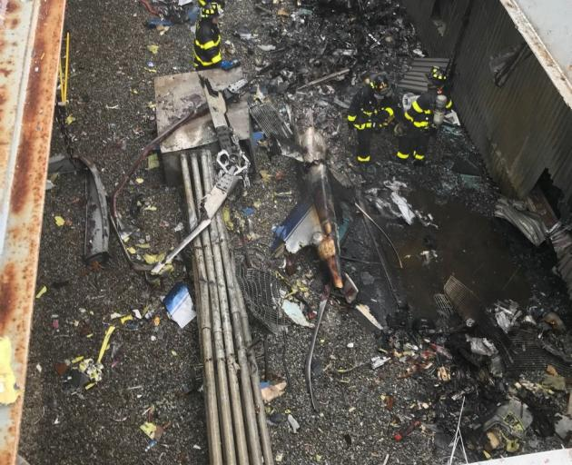 Emergency crews survey damage on the rooftop of the building. Photo: New York City Fire...