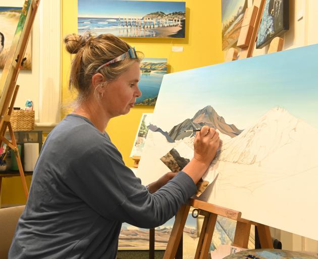 Dunedin artist Jayne Schwenke paints a landscape with oils.