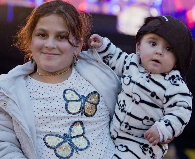 Ebtihal Alghanem (11) and her baby sister Jacinda Ahmad (6 months), who is named after Prime Minister Jacinda Ardern, rock out to Dunedin band Saurian at the New Years Eve Octagon party. Photo: Christine O'Connor