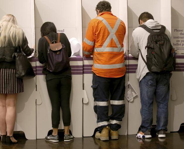 Voters fill in their ballots at Town Hall in Sydney on Saturday. Photo: AP