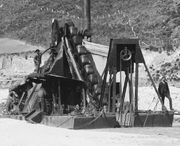 The Sew Hoy dredge at work in its pond at Big Beach, on the Shotover River. The smokestack of the...