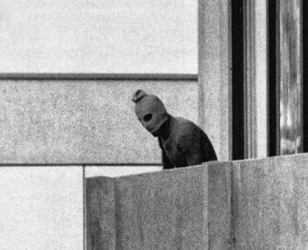 A masked member of the Black September terrorist group stands on the balcony of the apartment where the group held its hostages during the Munich Massacr