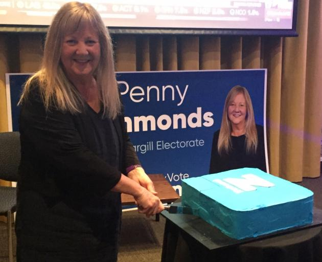 Penny Simmonds cuts a National party cake in relief tonight. Photo: Luisa Girao
