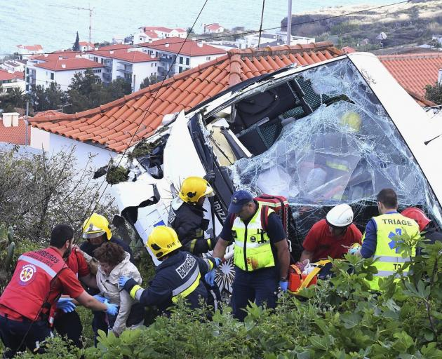 Injured passengers are taken from the bus after the crash on Madeira Island. Photo: Global...