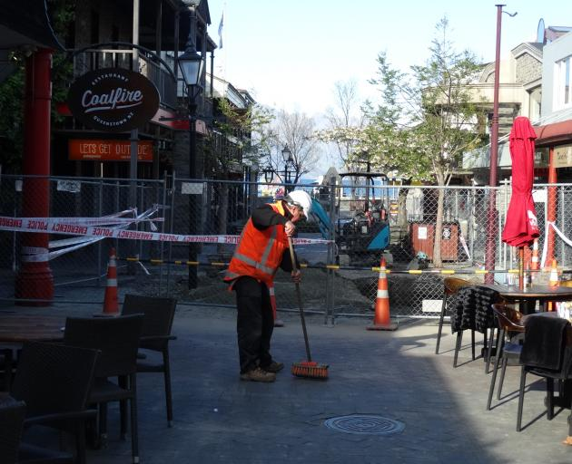 A contractor cleaning silt in Queenstown Mall this morning. Photo: Paul Taylor