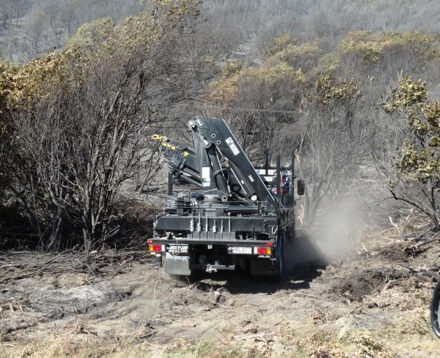 A Delta truck navigates through charred native scrub to work on reinstating power lines. Photo:...
