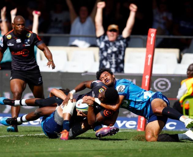 Sharks playet Aphelele Fassi crashes over to score a try despite the tackle from Melani Nanai of...