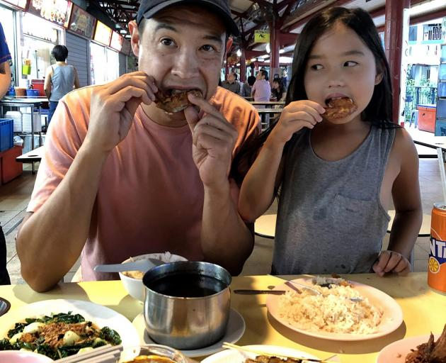 David Pierson eating fried chicken wings with his daughter, Ella, at Toa Payoh Lorong Food Centre.