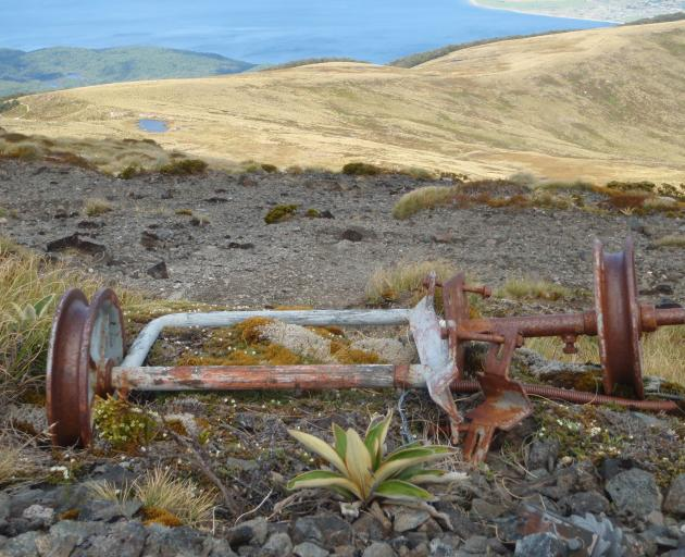 A rusty rope tow pulley is all that is left from a would-be ski field on Mt Luxmore. The roof of...