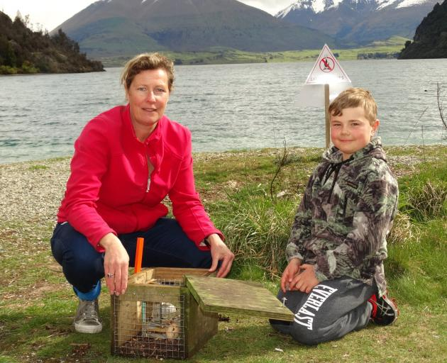 Wakatipu Wildlife Trust founding member Pippa Speedy and son Tommy (7) re-bait a possum trap at...
