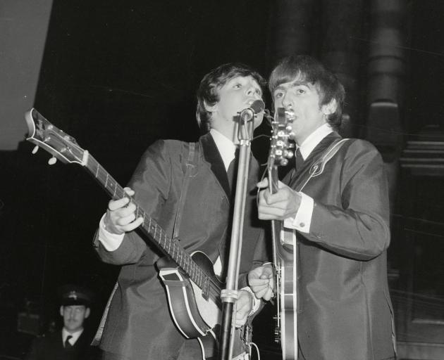 Paul McCartney (left) and George Harrison perform on stage  in Dunedin 57 years ago.