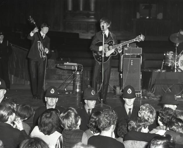 A line of police officers separates The Beatles from the crowd.
