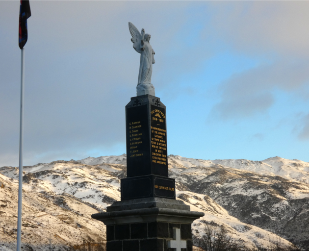 The Clyde War Memorial on Matau St as the sun breaks on the snow-covered Cairnmuir Range above Lake Dunstan. Photo: Jared Morgan