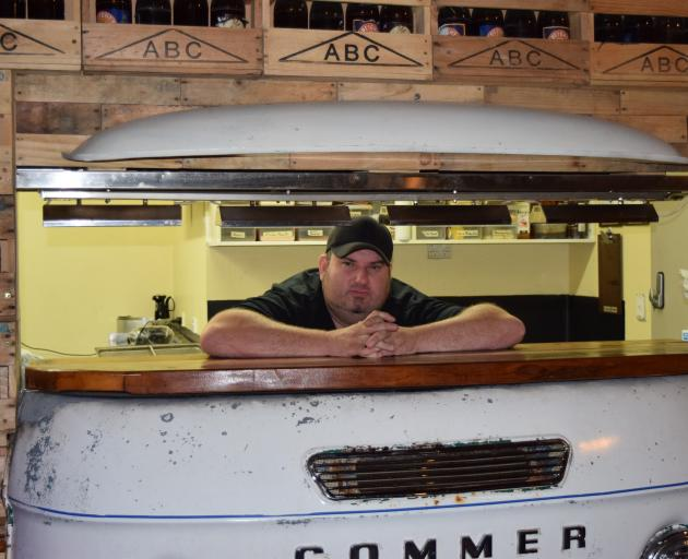 Fifty Gorillas Grill &  Venue owner Ian Lindsay relaxes on a  food serving counter made from a...