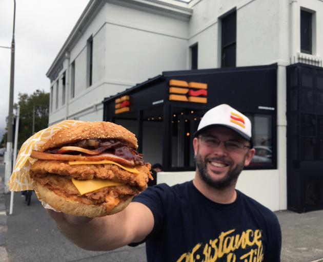 Re:Burger owner Boris Reiber presents one of his creations outside his store in North Dunedin....
