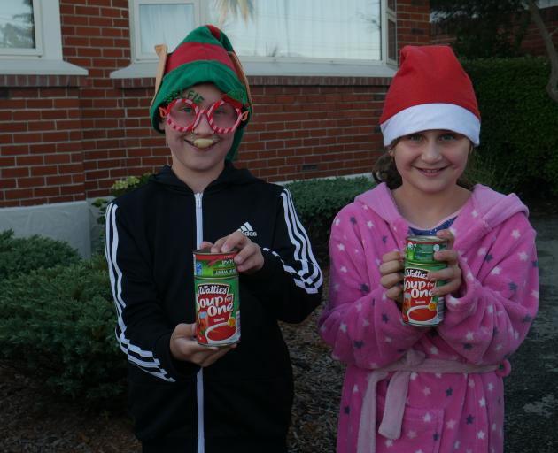 Siblings Alex (11, left) and Darcy (9) Tavendale wait for their cans to be collected during the...