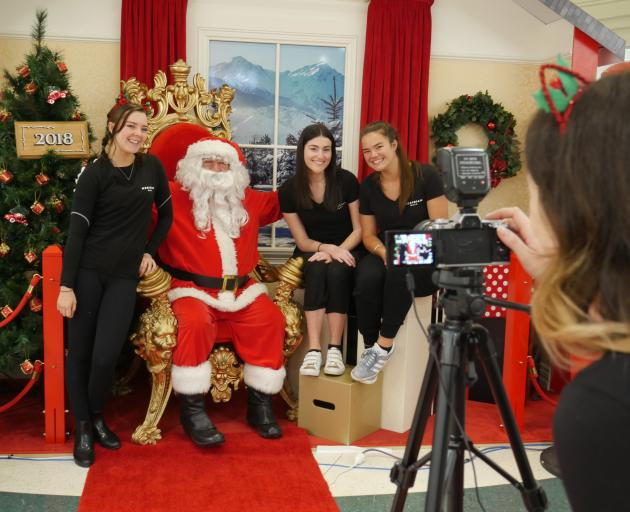 Santa and his helpers (from left) Emma Stokes, Paris Rolton and Hannah Hedges smile for the...