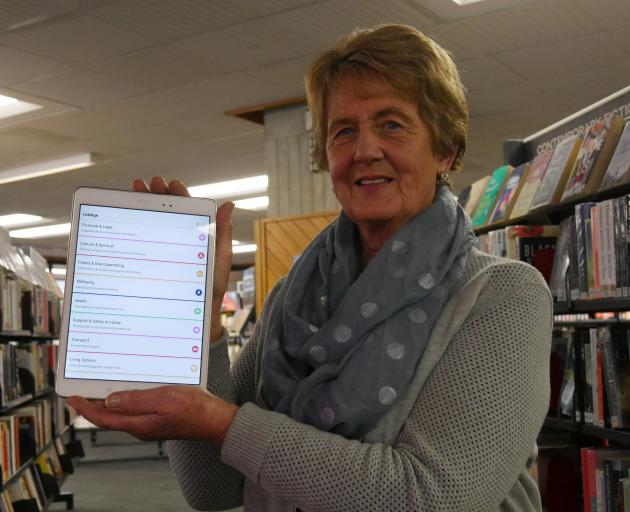 LinkAge working group consumer representative Juliet Kenworthy holds a tablet with the new...