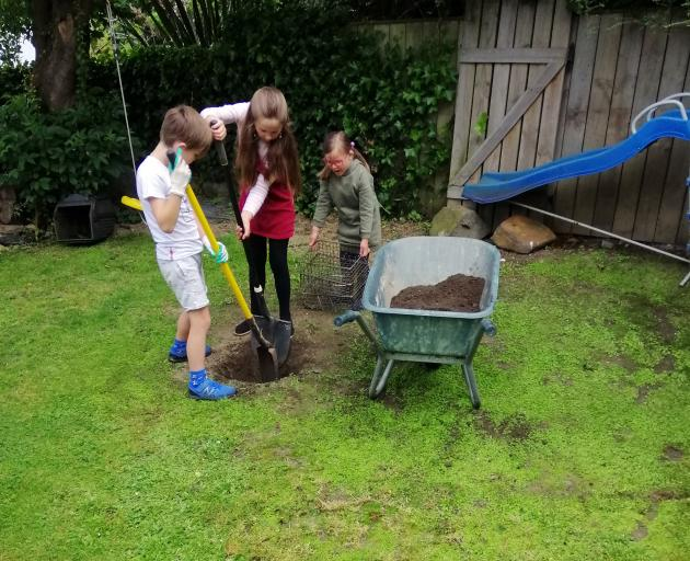 Siblings Oskar, Anika and Emily Doidge dig a hangi pit at their City Rise home. Photo: supplied