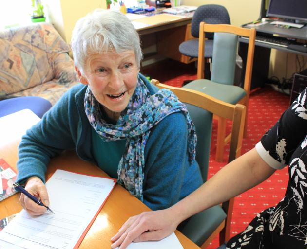 SuperGran's Dunedin manager Marie Sutherland prepares some life skills information for a client...