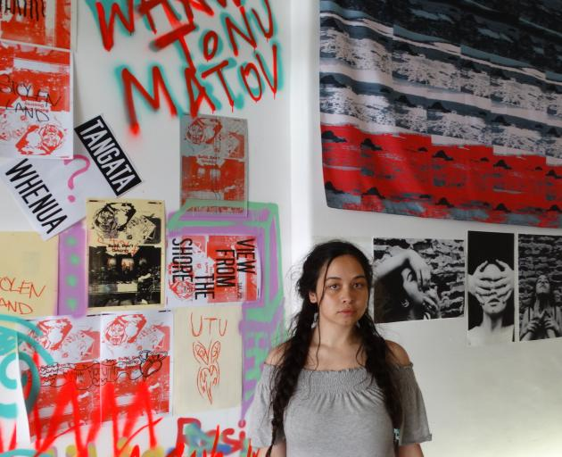 Dunedin artist Teah Paterson is flanked by her own work (right), focusing on the mana wahine...