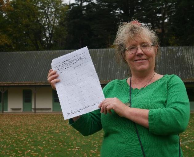 North East Valley resident Kaitrin McMullan holds a petition urging the Dunedin City Council to...