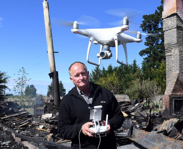 Stephen Jaquiery uses a drone to shoot video of a house fire aftermath at Mt Stoker. PHOTO: DAISY...