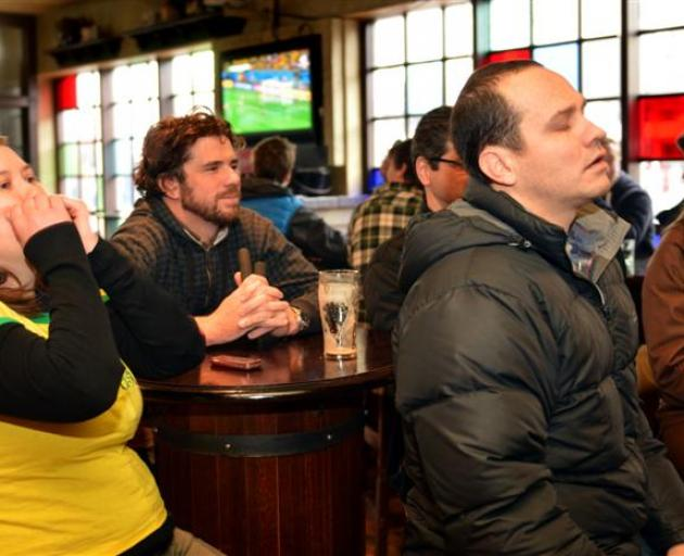 Brazil supporters (from left) Carolina Loch, of Florianopolis, Nathan Keen, of Dunedin, and DJ Zanicotti, in The Bog Irish Bar in Dunedin yesterday watch their team get beaten by Germany in the Fifa World Cup semifinal. Photo by Stephen Jaquiery