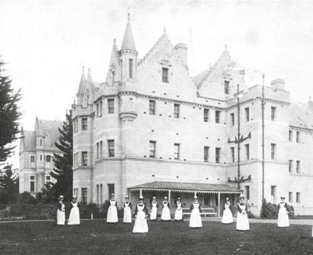 Seacliff Lunatic Asylum nursing staff pose on the lawn in front of the building, c 1890, in this...