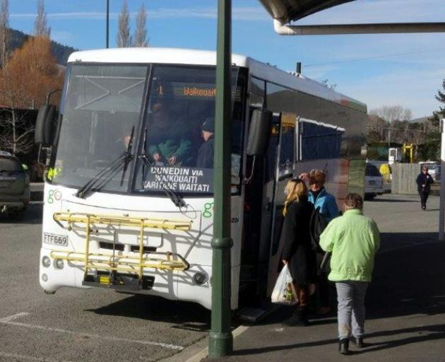 Passengers board a bus in Bond St yesterday. Buses are still calling at the old stop. Photo by Bill Campbell.