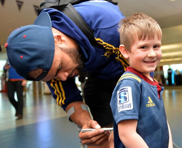 Young Highlanders fan Beau Glover (4) gets his jersey signed by winger Patrick Osborne at Dunedin International Airport yesterday. Photo by Stephen Jaquiery.