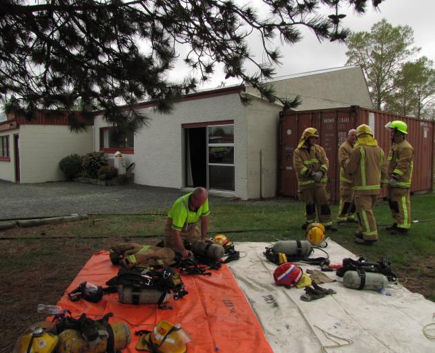 Ranfurly firefighters arrange gear outside the Maniototo Arts Centre after battling a fire. Photo by Jono Edwards.