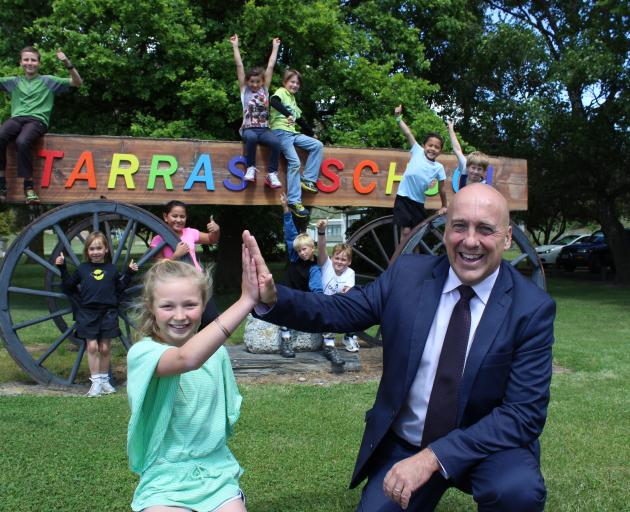 Tarras School pupil Billie Willson (10) high-fives Central Otago Mayor Tim Cadogan yesterday after an announcement the settlement's toilet problems will soon be over, while the school's other pupils celebrate. They are (from left) Jack Willson (13), Aster