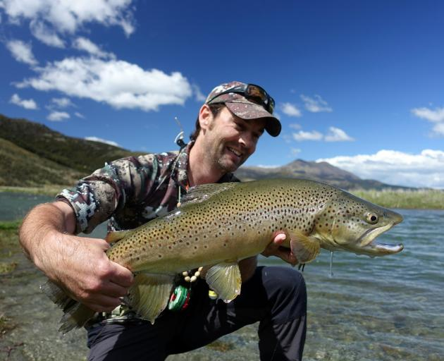 Fish & Game communications officer Hamish Carnachan, from Wellington, with an upper Oreti River treasure, a big brown trout. Photo from Fish & Game.