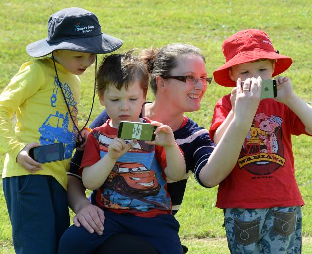 Playing an augmented reality smartphone game at Caversham Reserve yesterday are Eloise Sime and her sons (from left) Charlie (6), Quintin (4) and Lachlan (4). Photo by Linda Robertson.