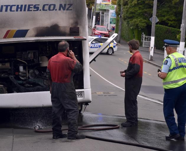 Ritchies Coachlines engineers inspect a fire-damaged engine bay of a bus in Dunedin yesterday. Photo by Craig Baxter.
