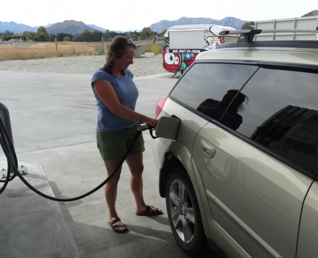 Rebecca Kirby-Crowe takes advantage of cheaper fuel at the McKeown fuel station in Wanaka. Photo by Kerrie Waterworth.