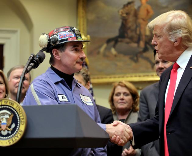President Donald Trump shakes the hand of a coal miner at a signing ceremony last week to repeal...