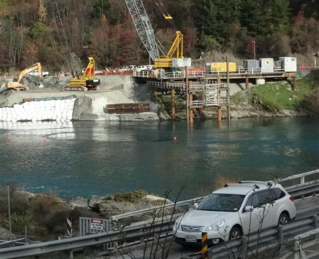 A vehicle crosses the  Kawarau Falls bridge while construction of the  replacement bridge...