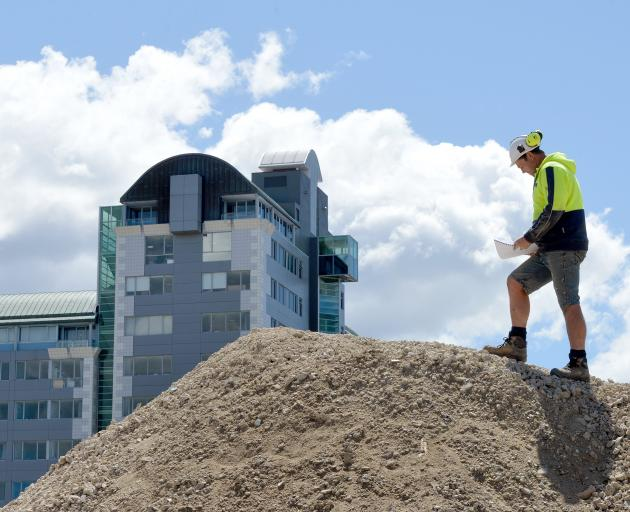 Fourth-quarter GDP expected to wane, but construction remains strong. Pictured, Cook Brothers Construction site foreman Scott Milne checks plans at the former Wickliffe Press site in January, while the Commerce building (background) is undergoing a multim