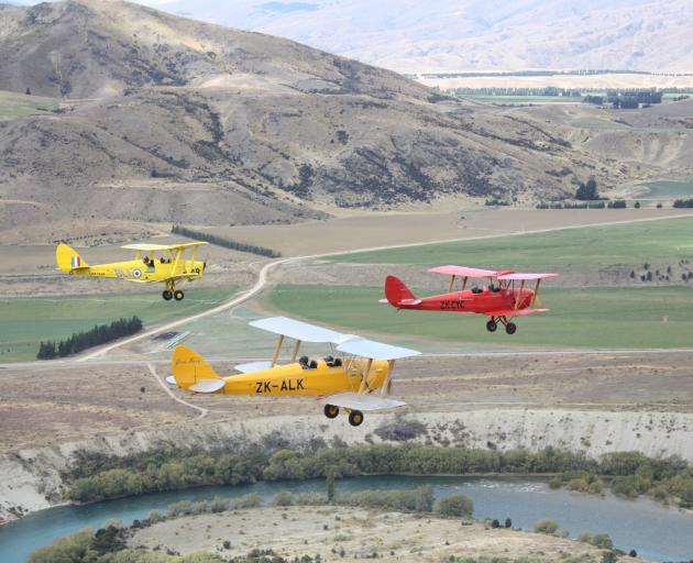 Three Tiger Moths fly in formation over the Clutha River south of Luggate, towards Bendigo and on to Alexandra after leaving Wanaka Airport yesterday afternoon. The planes are part of a group of vintage aircraft, mainly made up of Tiger Moths, on a flying