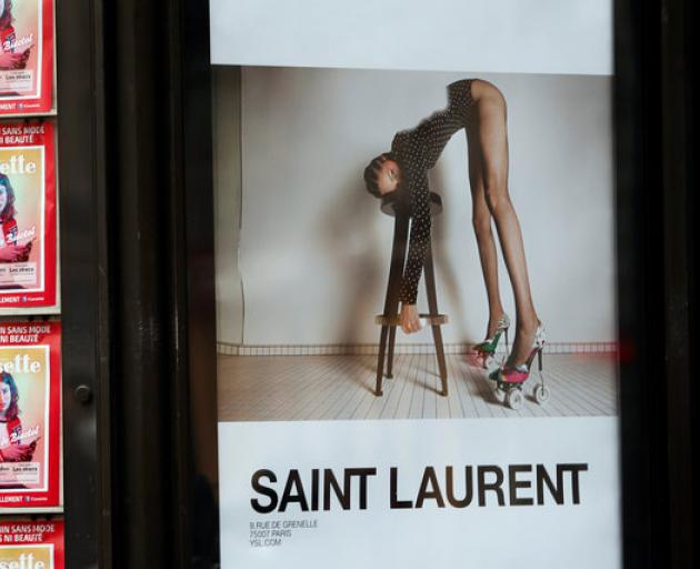 An ad by French fashion house Yves Saint Laurent is seen on a newspaper kiosk in Paris. Photo: Reuters