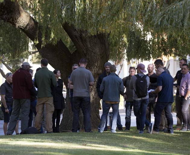 A group of plainclothes police and security wait outside reception at Millbrook Resort, Arrowtown...