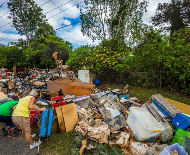 Locals sift through belongings at Eagleby in Queensland after floods hit the area in the wake of...