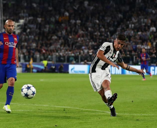 Paulo Dybala melepaskan tembakan ke gawang Barcelona
