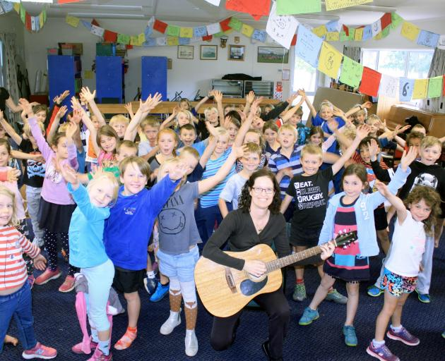 Cathy Irons (centre) leads a group of Hawea Flat School year 3 and 4 pupils through a song yesterday. Photo by Tim Miller.