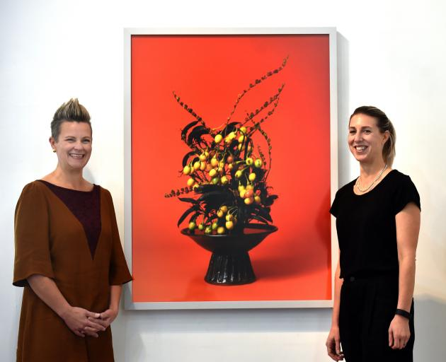 Milford Gallery curators Lisa Wilkie (left) and Vanessa Jones with Ann Shelton's The Courtesan, Poroporo (Solanum sp.). Photo: Peter McIntosh.