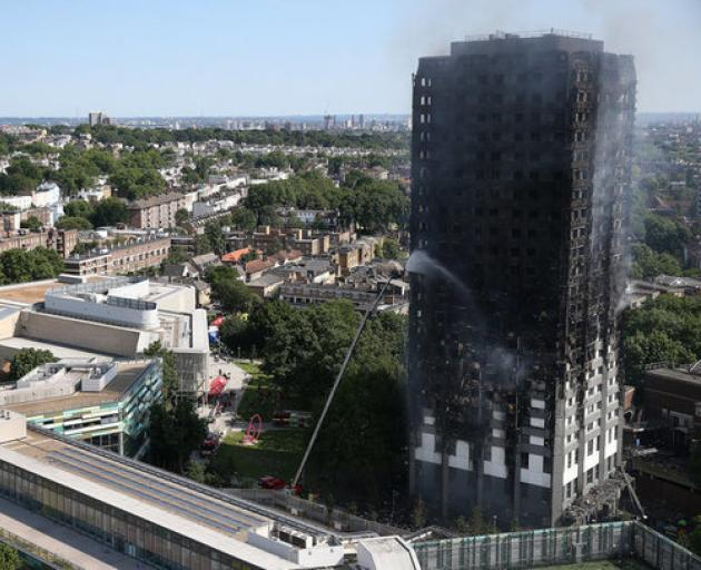 A firefighter directs a jet of water at a tower block severely damaged by a serious fire in West London. Photo: Reuters