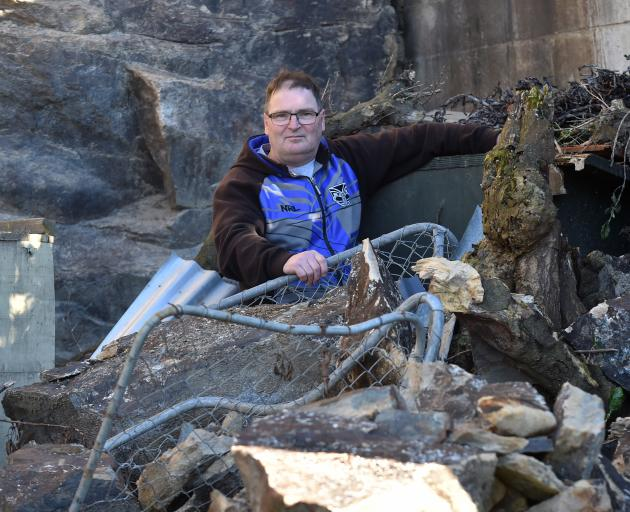 Dunedin resident Ashley Boorer is keeping a nervous eye on the cliff above his home, after a boulder estimated to weigh more than a tonne crashed down, destroying his dog kennel run. Photo: Peter McIntosh