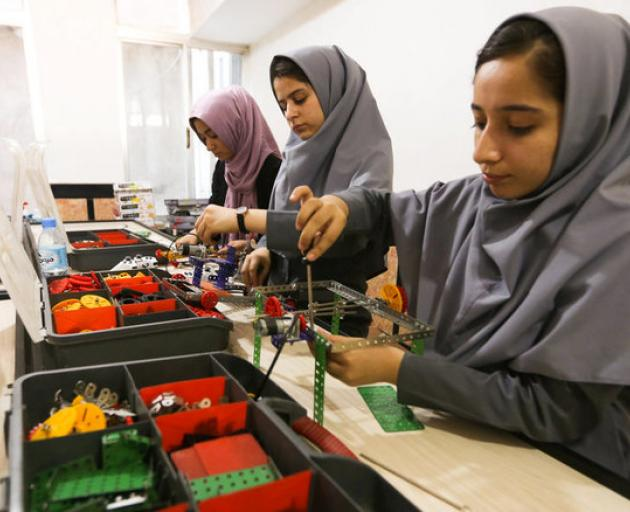 Members of Afghan robotics girls team which was denied entry into the United States for a competition, work on their robots in Herat province. Photo: Reuters